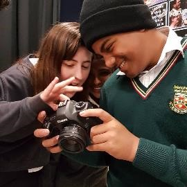 Two people holding a camera and smiling.