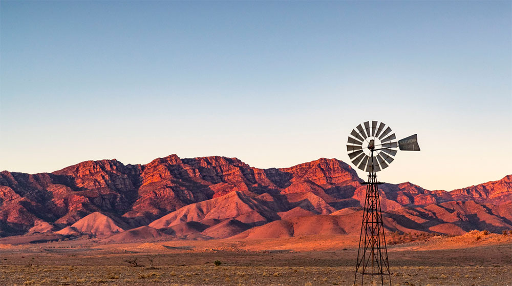 Windmill with picturesque red mountain behind