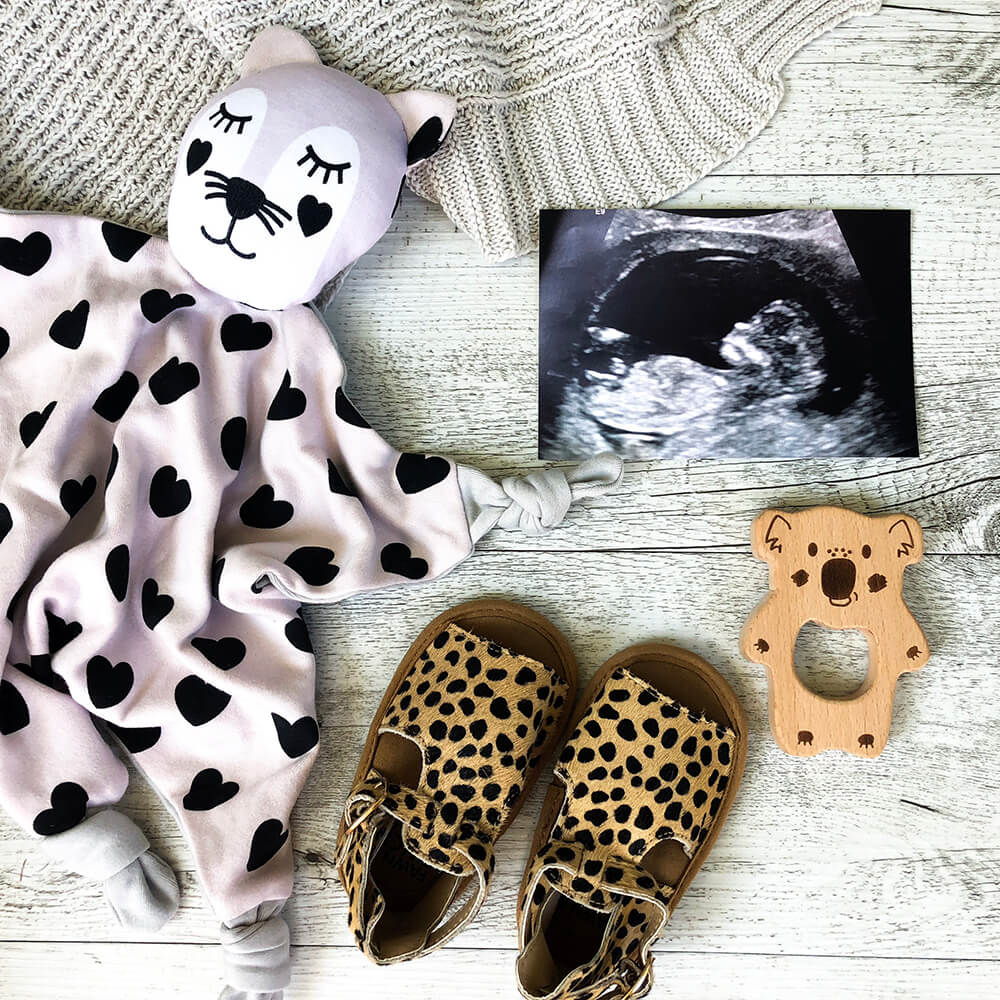 Ultrasound, baby clothes and pair of shoes
