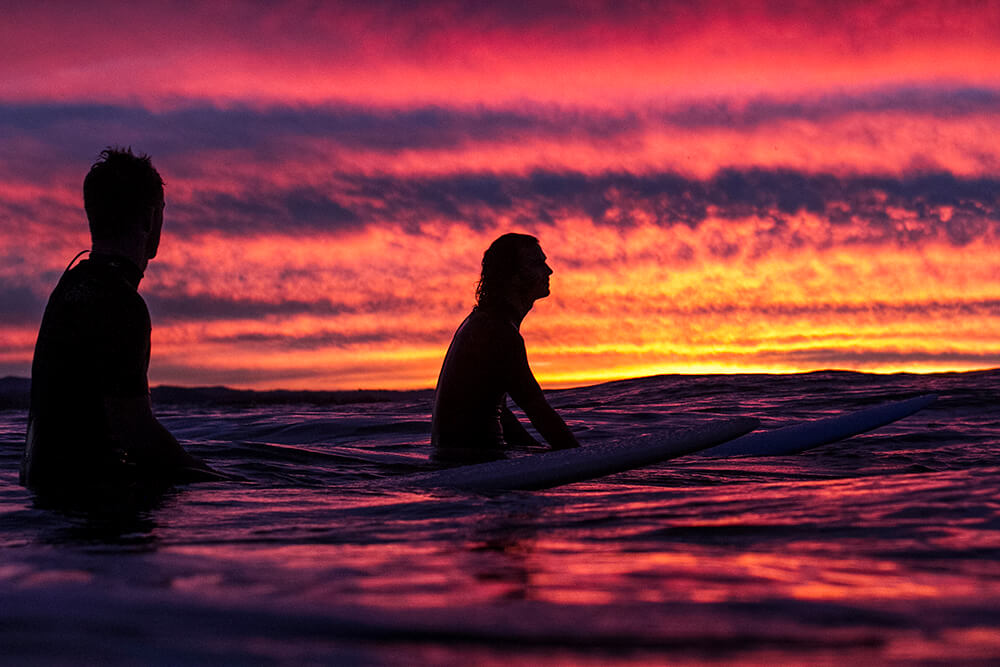 Portrait image of surfers at sunset