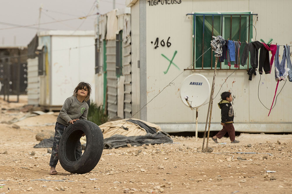 image of a refugee kid playing with tyre