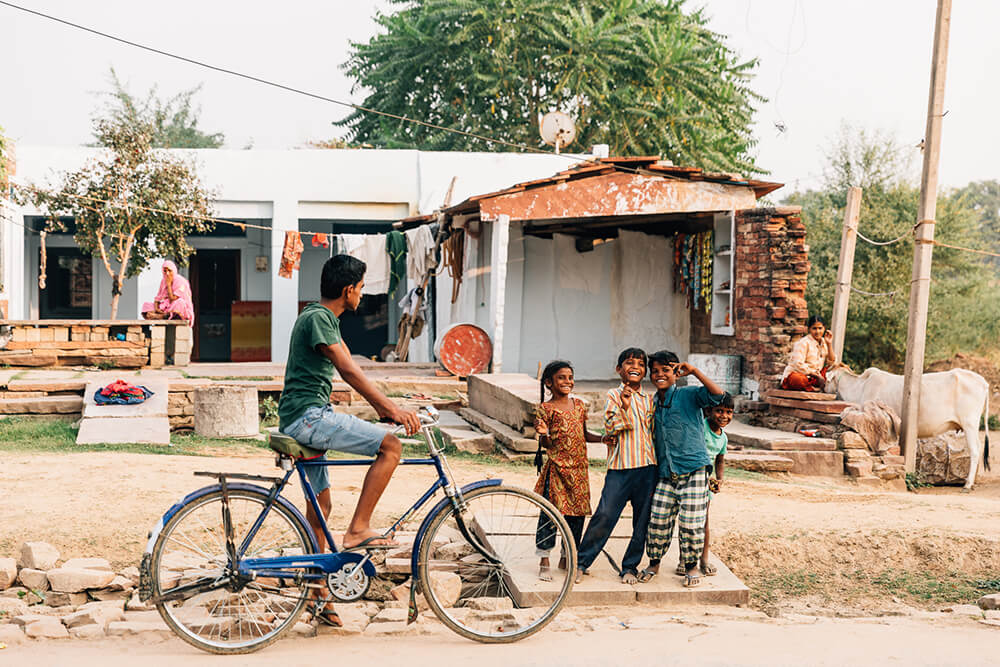 Photo of a cyclist and kids in a street in India. Image by Melissa Findley