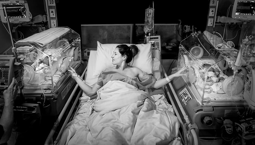 image of new mother in hospital bed with twins in incubator on either side