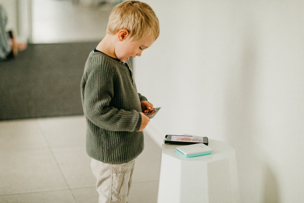 Toddler with mini photo printer